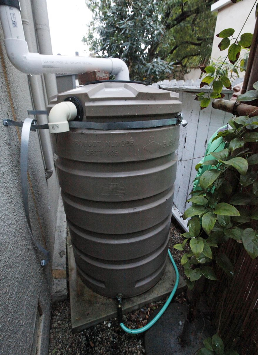 This Feb. 28, 2014 photo shows a 200-gallon water storage tank that collects rain from the roof of Josephine Miller's home in Santa Monica, Calif., which she uses to water her garden. With California in a drought, some communities in recent years have turned to water conservation measures in an effort to cut down on imported water.  (AP Photo/Reed Saxon)