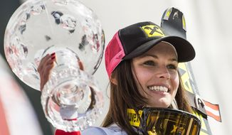 Anna Fenninger of Austria poses with the overall World Cup trophy at the alpine skiing World Cup finals in Lenzerheide, Switzerland, Sunday, March 16, 2014. (AP Photo/Keystone, Jean-Christophe Bott)
