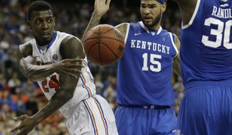 Florida forward Casey Prather (24) passes the ball against Kentucky forward Willie Cauley-Stein (15) and Kentucky forward Julius Randle (30) during the second half of an NCAA college basketball game in the Championship round of the Southeastern Conference men's tournament, Sunday, March 16, 2014, in Atlanta. (AP Photo/Steve Helber)