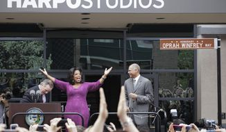 """File-This May 11, 2011, file photo shows talk-show host Oprah Winfrey reacting after a street outside her Harpo Studios in Chicago was proclaimed """"Oprah Winfrey Way"""" during a ceremony with Chicago Mayor Richard M. Daley, left, and Bobby Ware, commissioner of the Chicago Department of Transportation.  Winfrey is selling Harpo Studios in Chicago to a developer, but the studio will remain on the property for another two years. Harpo Inc. said in a statement that it has entered into a purchasing agreement with Sterling Bay Cos. for the four-building campus on Chicago's West Side. (AP Photo/M. Spencer Green,File)"""