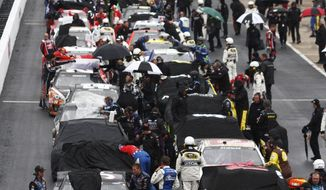 Crew members cover the cars during a weather delay during the NASCAR Sprint Cup series auto race at Bristol Motor Speedway on Sunday, March 16, 2014, in Bristol, Tenn. (AP Photo/Wade Payne)