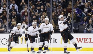 Anaheim Ducks left wing Patrick Maroon, right, celebrates his goal along with teammates, from left to right, Nick Bonino, Kyle Palmieri, and Ben Lovejoy, against the Los Angeles Kings during the second period of an NHL hockey game in Los Angeles, Saturday, March 15, 2014. (AP Photo/Danny Moloshok)