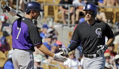 Colorado Rockies' Matt McBride (7) greets Nolan Arenado after a solo home run in the sixth inning of a spring exhibition baseball game against the Los Angeles Dodgers, Sunday, March 16, 2014, in Glendale, Ariz. (AP Photo/Mark Duncan)