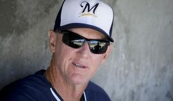 Milwaukee Brewers manager Ron Roenicke sits in the dugout before a spring exhibition baseball game against the Arizona Diamondbacks in Scottsdale, Ariz., Sunday, March 16, 2014. (AP Photo/Chris Carlson)
