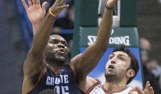 Milwaukee Bucks' Zaza Pachulia (27) and Brandon Knight defend against Charlotte Bobcats' Al Jefferson during the second half of an NBA basketball game on Sunday, March 16, 2014, in Milwaukee. (AP Photo/Tom Lynn)