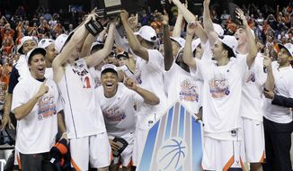 Virginia players celebrate with the trophy after defeating Duke in an NCAA college basketball game in the championship of the Atlantic Coast Conference tournament in Greensboro, N.C., Sunday, March 16, 2014. Virginia won 72-63. (AP Photo/Gerry Broome)