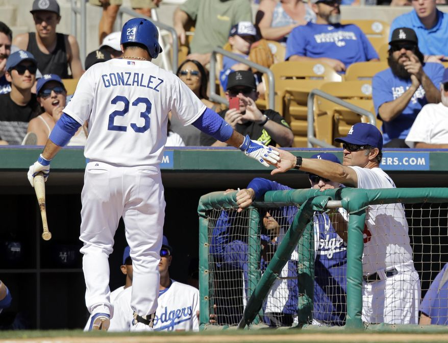 Los Angeles Dodgers manager Don Mattingly, right, congratulates Adrian Gonzalez (23) after Gonzalez's sacrifice fly in the fifth inning drove in a run against the Colorado Rockies in a spring exhibition baseball game, Sunday, March 16, 2014, in Glendale, Ariz. (AP Photo/Mark Duncan)
