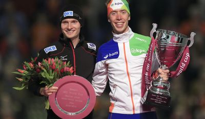 Second place Patrick Beckert of Germany, left, and winner Jorrit Bergsma of the Netherlands pose without third place Sven Kramer of The Netherlands after the men's 5000-meter speedskating race during the World Cup final at Thialf skating arena, Sunday, March 16, 2014, in Heerenveen, northern Netherlands. Kramer did not compete as he is recovering from an operation. (AP Photo/Peter Dejong)