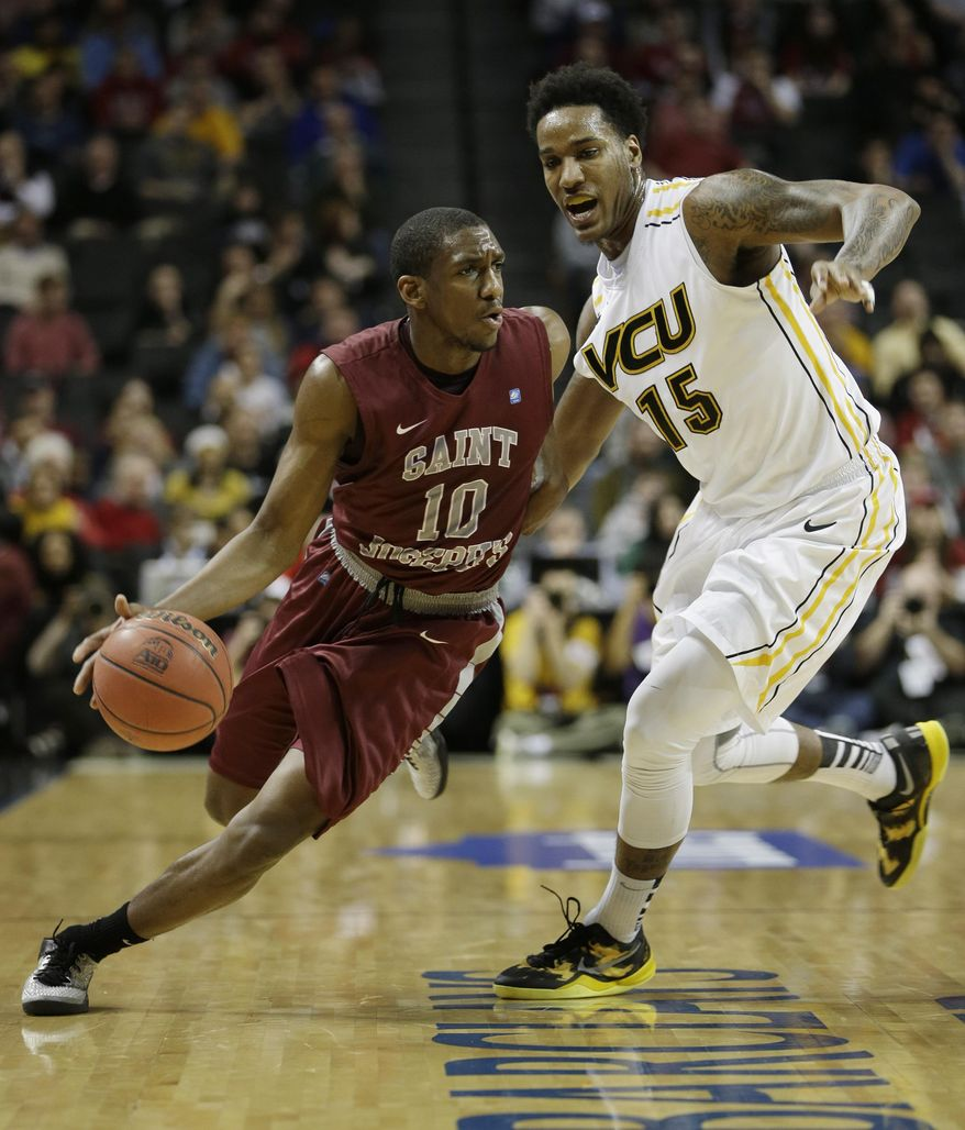 Saint Joseph's Langston Galloway, left, moves past VCU's Juvonte Reddic during the first half of an NCAA college basketball game in the championship round of the Atlantic 10 Conference tournament at the Barclays Center in New York, Sunday, March 16, 2014. (AP Photo/Seth Wenig)