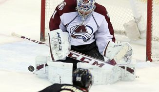 Colorado Avalanche goaltender Semyon Varlamov, top, makes a stop against Ottawa Senators' Mika Zibanejad during NHL hockey game action in Ottawa, Ontario, Sunday, March 16, 2014. (AP Photo/The Canadian Press, Fred Chartrand)