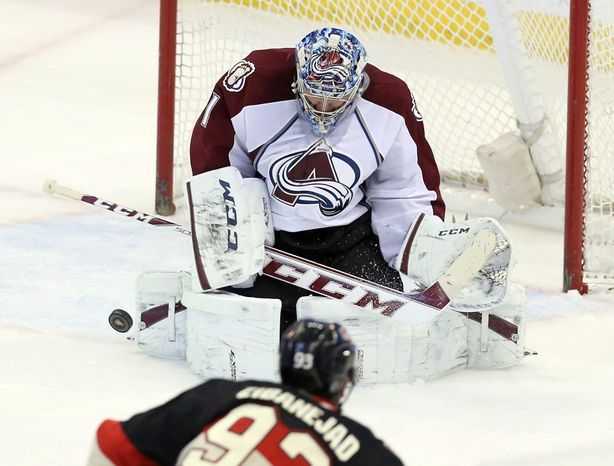 Colorado Avalanche goaltender Semyon Varlamov, top, makes a stop against Ottawa Senators' Mika Zibanejad during NHL hockey game action in Ottawa, On