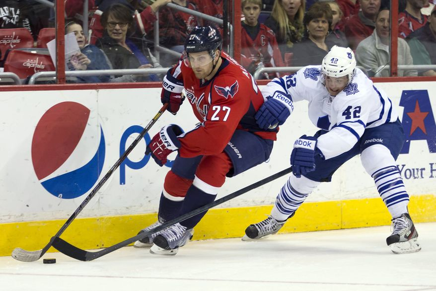 Toronto Maple Leafs center Tyler Bozak (42) defends against Washington Capitals defenseman Karl Alzner (27) during the first period of an NHL hockey game on Sunday, March 16, 2014, in Washington. (AP Photo/ Evan Vucci)