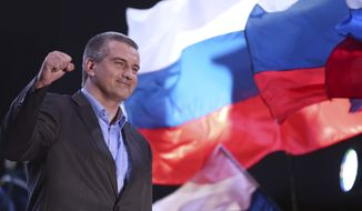 The head of Crimea's Russia-backed leader Sergei Aksyonov gestures as people celebrate in Lenin Square, in downtown Simferopol, Ukraine, Sunday, March 16, 2014. Polls have closed in Crimea's contentious referendum on seceding from Ukraine and seeking annexation by Russia. The vote, unrecognized both by the Ukrainian government and the West, was held Sunday as Russian flags fluttered in the breeze and retirees grew weepy at the thought of reuniting with Russia. (AP Photo/Max Vetrov)