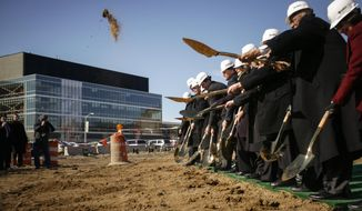 Officials from Michigan State University, U.S. Senators, State Representatives, and others, including Chairman of the MSU Board of Trustees Joel Ferguson, second from left,  break ground in East Lansing, Mich. at the future home of the Facility for Rare Isotope Beams at a special groundbreaking ceremony, Monday, March 17. 2014. (AP Photo/The Lansing State Journal, Matthew Dae Smith)