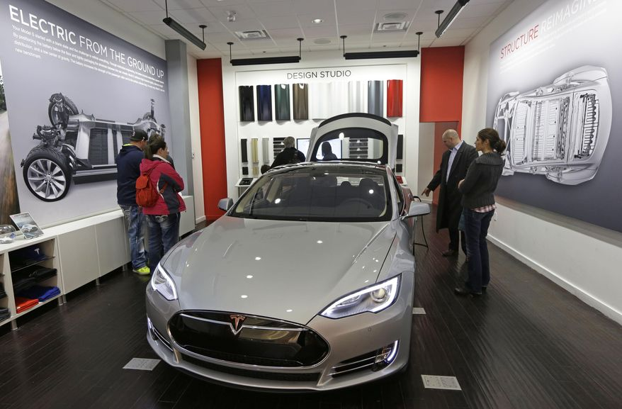 Customers check out a new Tesla all electric car, Monday, March 17, 2014, at a Tesla showroom inside the Kenwood Towne Centre in Cincinnati. Ohio auto dealers are sparring at the Statehouse with the California-based Tesla, which is selling it's next generation electric cars from three Ohio storefronts. Lawmakers in Ohio and other states are trying to block Tesla direct sales on grounds they undercut traditional auto dealerships. (AP Photo/Al Behrman)
