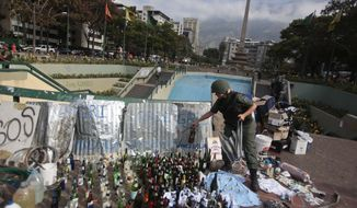 A Bolivarian National Guard places a glass bottles with others items allegedly seized from demonstrators after a raid in Plaza Altamira, Caracas, Venezuela, Monday, March 17, 2014. The Bolivarian National Guard conducted raids in the Chacao district this Monday morning vacating the barricades installed there in order to prevent anti-government protests from happening in the area. (AP Photo/Esteban Felix)