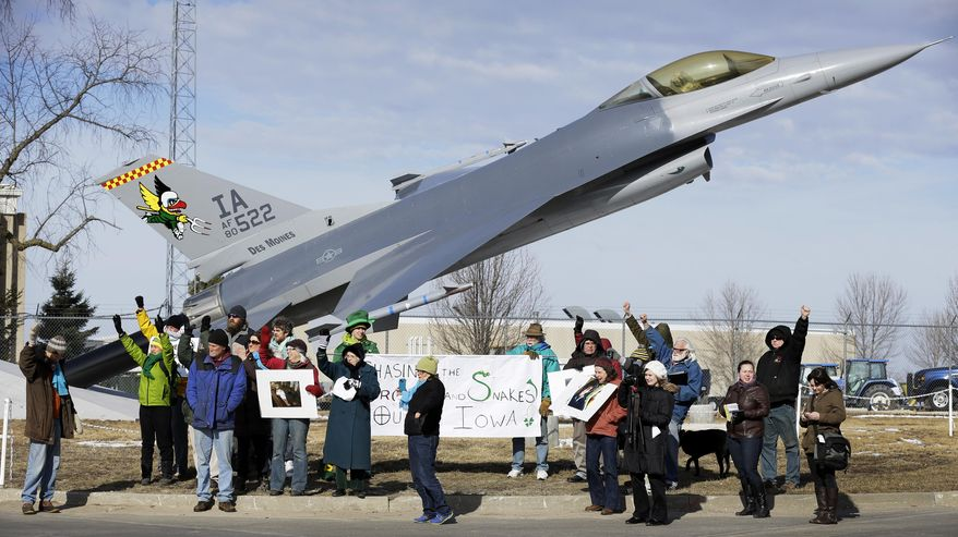 Protesters rally outside the Iowa Air National Guard base, Monday, March 17, 2014, in Des Moines, Iowa. Seven protesters, who were rallying against the use of drones to carry out military strikes, were arrested at the base. (AP Photo/Charlie Neibergall)