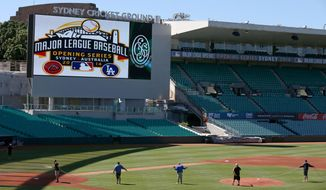 Ground staff prepare the baseball field that has been especial built for the Major League Baseball opening series at the Sydney Cricket Ground in Sydney, Monday, March 17, 2014. The MLB season-opening two-game series between the Los Angeles Dodgers and Arizona Diamondbacks in Sydney will be played this weekend. (AP Photo/Rick Rycroft)