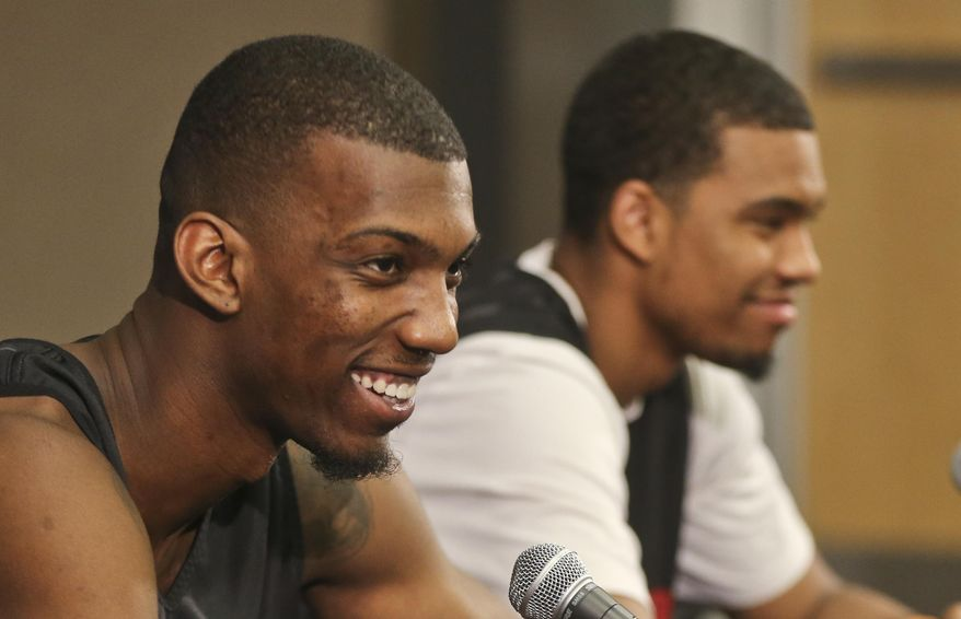 """San Diego State forward Winston Shepard produces a smile when asked about playing against New Mexico State's 7'5"""", 360 pound center  Sim Bhullar in the team's first round NCAA basketball tournament game at a press conference Monday, March 17, 2014, in San Diego. Next to Shepard is guard Aqeel Quinn. (AP Photo/Lenny Ignelzi)"""