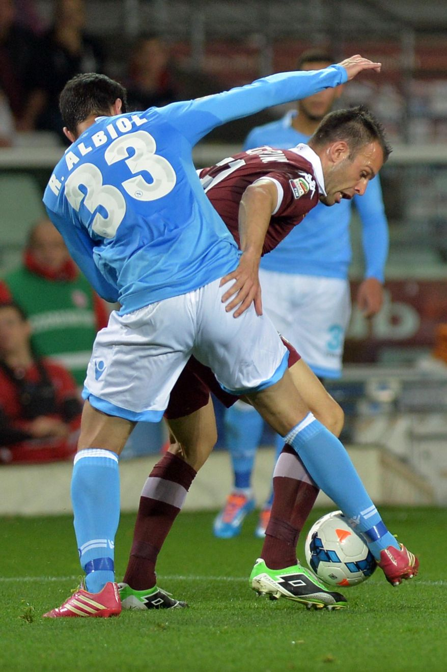 Torino forward Riccardo Meggiorini, right, challenges for the ball with Napoli defender Raul Albiol during a Serie A soccer match, at the Olympic  stadium, in Turin, Italy, Monday, March 17, 2014. (AP Photo/ Massimo Pinca)