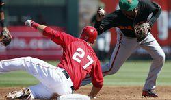 San Francisco Giants' Ehire Adrianza, right, throws to first base after forcing out Los Angeles Angels' Mike Trout (27) in the first inning of a spring training baseball game, Monday, March 17, 2014, in Tempe, Ariz. (AP Photo/Ross D. Franklin)