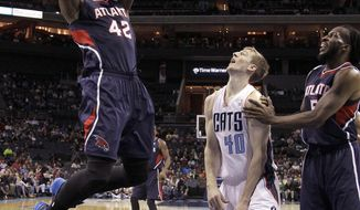 Atlanta Hawks's Elton Brand (42) goes up strong for the basket as Charlotte Bobcats's Cody Zeller (40) and Atlanta Hawks's DeMarre Carroll (5) watch during the first half of an NBA basketball game in Charlotte, N.C., Monday, March 17, 2014. (AP Photo/Bob Leverone)