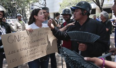 "A anti-government demonstrator, left, argues with a pro-government supporter inside of Plaza Altamira in Caracas, Venezuela, Monday, March 17, 2014. The cardboard sign the woman carries reads ins Spanish ""GNB please help us. The students have the ideas. The thugs have the guns.""  The pro-government sympathizers carry brooms to clean Plaza Altamira from debris left over from previous clashes. Security forces on Monday took control of the plaza and surrounding neighborhoods that have become the center of anti-government protests that have shaken the country for a month. (AP Photo/Esteban Felix)"
