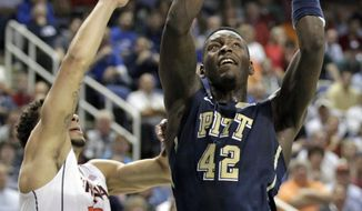 Pittsburgh's Talib Zanna (42) shoots past Virginia's Anthony Gill (13) during the first half of an NCAA college basketball game in the semifinals at the Atlantic Coast Conference tournament in Greensboro, N.C., Saturday, March 15, 2014. (AP Photo/Bob Leverone)