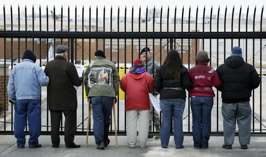 Protesters stand outside the entrance of the Iowa Air National Guard base before being arrested, Monday, March 17, 2014, in Des Moines, Iowa. The protesters were rallying against the use of drones to carry out military strikes. (AP Photo/Charlie Neibergall)