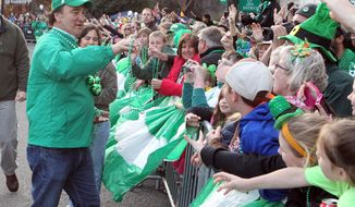 Actor Jim Belushi, left, makes his way down Bridge Street during what's being called the world's shortest St. Patrick's Day Parade, Monday, March 17, 2014, in Hot Springs Ark. Belushi was the grand marshal of the parade that featured 40 entries and was held on a street that is 98 feet long. (AP Photo/The Sentinel-Record, Richard Rasmussen)