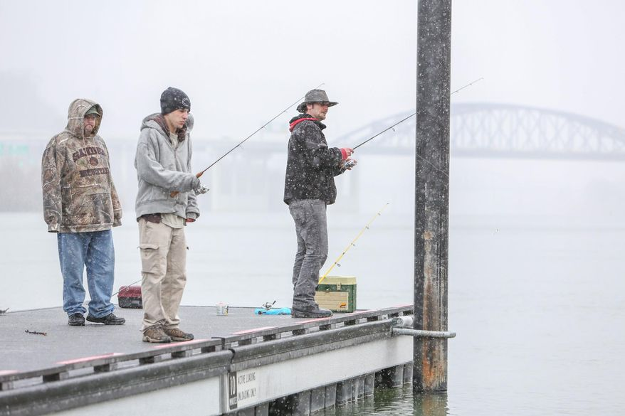 From right, Greg Holcomb, 33, John Carpenter, 25, and Dave Blackhurst, 34, all of Charleston, fish in the Kanawha River at Haddad Riverfront Park during a steady snow shower, Sunday, March 16, 2014, in Charleston, W.Va. (AP Photo/Charleston Daily Mail, Marcus Constantino)