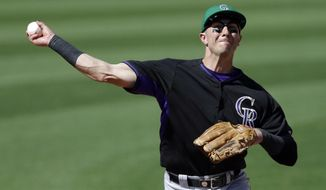 Colorado Rockies shortstop Troy Tulowitzki throws out San Diego Padres' Chris Denorfia at first during the fifth inning a spring exhibition baseball game Monday, March 17, 2014, in Peoria, Ariz. (AP Photo/Darron Cummings)