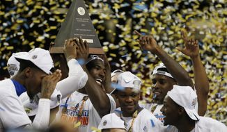 Florida center Patric Young (4) hills the SEC Championship trophy with his team mates after the second half of an NCAA college basketball game against Kentucky in the Championship round of the Southeastern Conference men's tournament, Sunday, March 16, 2014, in Atlanta. Florida won 61-60. (AP Photo/John Bazemore)