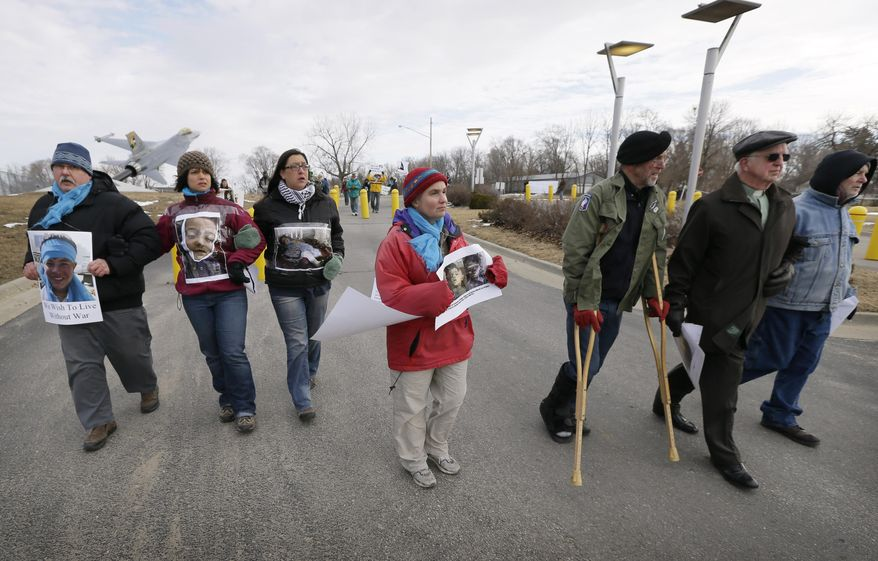 Protesters march to the entrance of the Iowa Air National Guard base before being arrested, Monday, March 17, 2014, in Des Moines, Iowa. The protesters were rallying against the use of drones to carry out military strikes. (AP Photo/Charlie Neibergall)