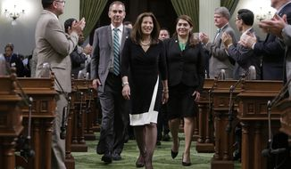 California Supreme Court Chief Justice Tani Cantil-Sakauye, center, is greeted by lawmakers as she walks to the Assembly podium to deliver her annual State of the Judiciary Address before a joint session of the Legislature at the Capitol in Sacramento, Calif., Monday, March 17, 2014. Saying years of budget cuts have forced courthouses to close, Cantil-Sakauye said the court system needs more money if it's going to recover from years of budget cuts. (AP Photo/Rich Pedroncelli)
