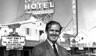 FILE - In this April 22, 1965 file photo provided by the Las Vegas News Bureau, casino owner Jackie Gaughan poses in front of his El Cortez Hotel and Casino in downtown Las Vegas. Gaughan, the Las Vegas gambling pioneer who once owned much of the downtown casino market, died Wednesday, March 12, 2014. He was 93. Gaughan is most closely associated with the El Cortez casino, which he bought in 1963. He later transferred ownership of the historic casino, but lived in a penthouse apartment there into his 90s and was known to play poker in the casino almost every day. (AP Photo/Las Vegas News Bureau, File)