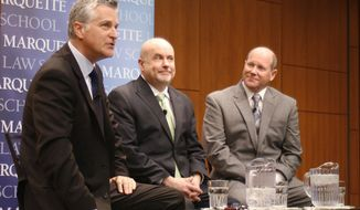 U.S. Reps. Mark Pocan, center, and Reid Ribble, right, listen to moderator Mike Gousha during a panel discussion Monday, March 17, 2014, at Marquette University Law School in Milwaukee. Ribble, a Republican from the Fox Valley, and Pocan, a Madison Democrat, belong to No Labels Problem Solvers, a bipartisan group of lawmakers who meet weekly to get to know each other and discuss issues. (AP Photo/M.L. Johnson)