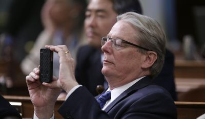 State Sen. William Monning, D-Carmel, takes a cell phone photo of California Supreme Court Chief Justice Tani Cantil-Sakauye as she delivers her annual State of the Judiciary Address before a joint session of the Legislature at the Capitol in Sacramento, Calif., Monday, March 17, 2014.  Cantil-Sakauye said the court system needs more money  if it's going to recover from years of budget cuts. (AP Photo/Rich Pedroncelli)