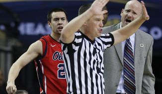 Mississippi head coach Andy Kennedy, right, and Mississippi guard Marshall Henderson (22) speak with an official during the second half of an NCAA college basketball game against Georgia in the quarterfinal round of the Southeastern Conference men's tournament, Friday, March 14, 2014, in Atlanta. (AP Photo/John Bazemore)