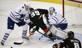 Anaheim Ducks' Matt Beleskey, center, is defended by Toronto Maple Leafs' Dion Phaneuf, left, as he tries to score against Toronto Maple Leafs goalie Jonathan Bernier during the third period of an NHL hockey game on Monday, March 10, 2014, in Anaheim, Calif. The Maple Leafs won 3-1. (AP Photo/Jae C. Hong)
