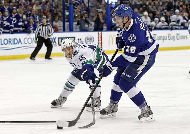 Tampa Bay Lightning left wing Ondrej Palat (18), of the Czech Republic, shoots and scores a goal around Vancouver Canucks center Jordan Schroeder (45) during the second period of an NHL hockey game Monday, March 17, 2014, in Tampa, Fla. (AP Photo/Brian Blanco)