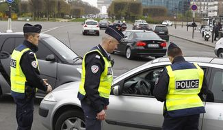Police officers control a vehicle in Paris, Monday, March 17, 2014. Cars with even-numbered license plates are prohibited from driving in Paris and its suburbs Monday, following a government decision over the weekend.  Paris is taking drastic measures to combat its worst air pollution in years, banning around half of the city's cars and trucks from its streets in an attempt to reduce the toxic smog that's shrouded the City of Light for more than a week. Visible in background is the Arc de Triomphe.(AP Photo/Remy de la Mauviniere)