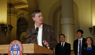 Colorado Gov. John Hickenlooper speaks to members of the media during a signing ceremony for a bill strengthening Colorado's marijuana packaging requirements, at the Capitol, in Denver, Monday March 17, 2014. Hickenlooper, who signed the bill into law, called it an important measure to make sure minors don't illegally access marijuana. Behind him, right to left, are state senator and bill co-sponsor Linda Newell, Dr. George Sam Wang, an emergency room physician at Children's Hospital Colorado, and state rep. and bill co-sponsor Daniel Kagan. (AP Photo/Brennan Linsley)