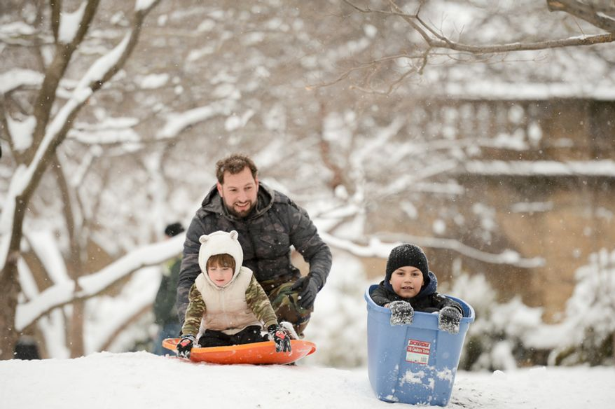Alberto Otero of Washington, D.C., left, helps his two sons Amaro, 7, and Eli, 2, sled in Meridian Hill Park as the region gets another snow storm, Washington, D.C., Monday, March 17, 2014. (Andrew Harnik/The Washington Times)