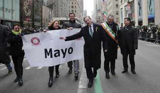 Irish Prime Minister Enda Kenny, center,marches in the St. Patrick's Day parade, Monday, March 17, 2014 in New York. The city's parade stepped off Monday without Mayor Bill de Blasio marching along with the crowds of kilted Irish-Americans and bagpipers amid a dispute over whether participants can carry pro-gay signs. (AP Photo/Mark Lennihan)
