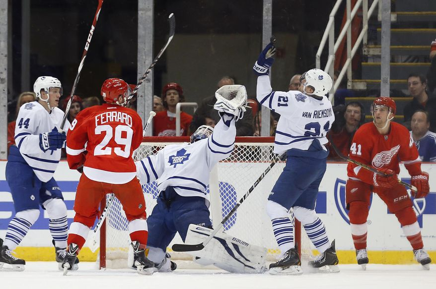 Toronto Maple Leafs goalie James Reimer, center, and James van Riemsdyk (21) reach up for the puck as Detroit Red Wings center Landon Ferraro (29) and Luke Glendening (41) stand near in the first period of an NHL hockey game in Detroit, Tuesday, March 18, 2014. (AP Photo/Paul Sancya)