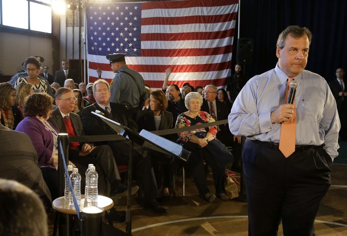 New Jersey Gov. Chris Christie, right, waits as police officers remove a woman, left, who was shouting at him during a town hall meeting Tuesday, March 18, 2014, in South River, N.J. Multiple protesters have disrupted Christie's town hall meeting. (AP Photo/Mel Evans)