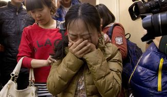 FILE - In this March 9, 2014 file photo, a Chinese relative of passengers aboard a missing Malaysia Airlines plane, center, cries as she is escorted by a woman while leaving a hotel room for relatives or friends of passengers aboard the missing airplane, in Beijing, China.  Ten days after Malaysia Airlines Flight 370 disappeared with 239 people aboard, an exhaustive international search has produced no sign of the Boeing 777, raising an unsettling question: What if the airplane is never found? (AP Photo/Andy Wong, File)