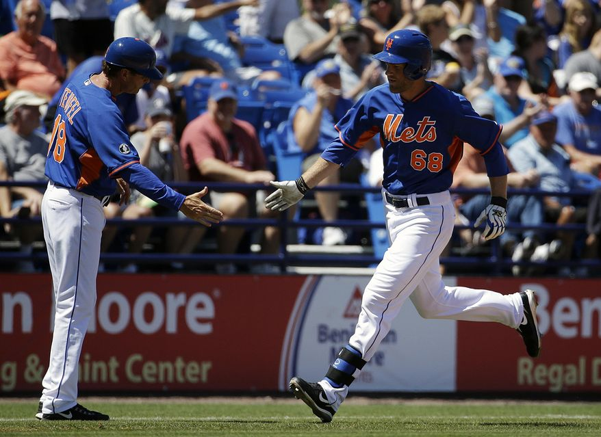 New York Mets' Eric Campbell, right, high-fives third base coach Tim Teufel after hitting a home run in the second inning of an exhibition spring training baseball game against the Detroit Tigers, Tuesday, March 18, 2014, in Port St. Lucie, Fla. (AP Photo/David Goldman)