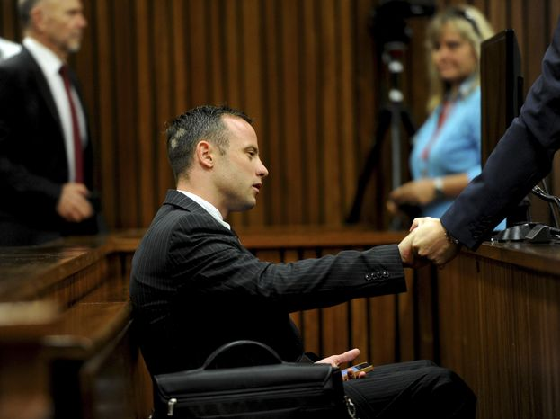Oscar Pistorius sits in the dock as he waits for proceedings to begin at a court in Pretoria, South Africa, Tuesday, March 18, 2014. Pistorius is on trial for the murder of his girlfrie